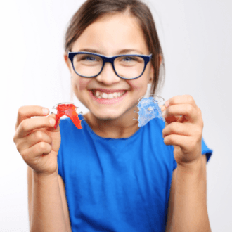 Teen girl holding up orthodontic appliances