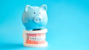 Piggy bank atop model teeth straightened by braces in Webster