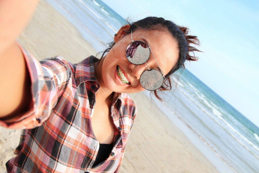 Woman with braces smiling while taking a selfie at the beach